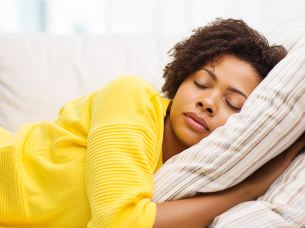 african young woman sleeping on sofa at home